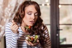 Jeune femme mangeant de la salade de légume frais photographie stock libre de droits