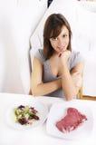 Jeune femme mangeant de la salade et de la viande image stock