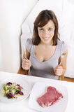 Jeune femme mangeant de la salade et de la viande photo libre de droits