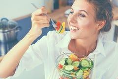 Jeune femme mangeant de la salade fraîche dans la cuisine moderne Images stock