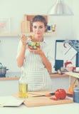 Jeune femme mangeant de la salade fraîche dans la cuisine moderne Photos stock