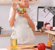 Jeune femme mangeant de la salade fraîche dans la cuisine moderne Photo stock