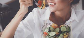 Jeune femme mangeant de la salade fraîche dans la cuisine moderne Photographie stock