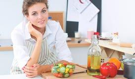 Jeune femme mangeant de la salade fraîche dans la cuisine moderne Photos libres de droits