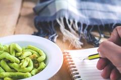 Jeune femme mangeant des casse-croûte tout en écrivant la lettre Images libres de droits