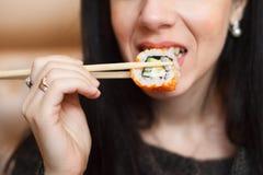 Jeune femme mangeant des sushi par des baguettes photographie stock libre de droits