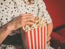 Jeune femme mangeant du maïs éclaté dans la salle de cinéma photographie stock