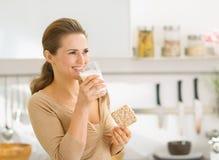 Jeune femme mangeant du pain croquant avec du lait photographie stock libre de droits