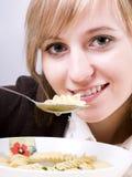 Jeune femme mangeant du potage Photo stock