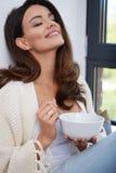 Jeune femme mangeant du potage photo libre de droits