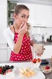 Jeune femme mangeant du yaourt avec des fruits frais pendant le matin Photos stock