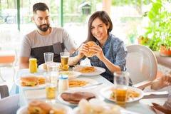 Jeune femme mangeant l'hamburger à un barbecue Image libre de droits