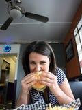 Jeune femme mangeant l'hamburger Photo stock