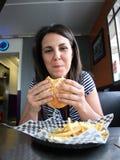 Jeune femme mangeant l'hamburger Photographie stock libre de droits