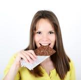 Jeune femme mangeant la barre de chocolat sur le fond blanc Photographie stock libre de droits