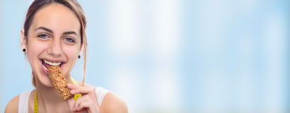 Jeune femme mangeant la barre de muesli Photographie stock