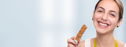 Jeune femme mangeant la barre de muesli Photo stock
