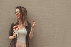 Jeune femme mangeant la gaufre de bulle avec les fruits, chocolat et guimauve, avec l'espace de copie Photos stock