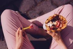 Jeune femme mangeant la gaufre de bulle avec les fruits, le chocolat et la guimauve, vue supérieure Photographie stock libre de droits