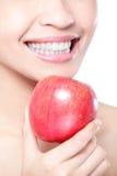 Jeune femme mangeant la pomme rouge avec des dents de santé Image stock