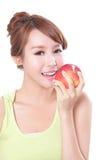 Jeune femme mangeant la pomme rouge avec des dents de santé Photos stock