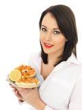 Jeune femme mangeant le bagel fumé de fromage de saumon et fondu Images libres de droits
