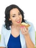 Jeune femme mangeant le biscuit entier avec le beurre d'arachide et Banan découpé en tranches Image stock