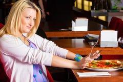 Jeune femme mangeant le dîner Photos libres de droits