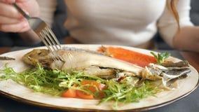 Jeune femme mangeant le dîner dans le restaurant Coupure du bifteck de poissons avec le couteau et la fourchette banque de vidéos