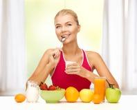 Jeune femme mangeant le petit déjeuner sain Photos stock