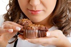 Jeune femme mangeant le petit pain de chocolat Images stock