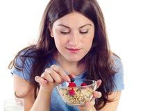 Jeune femme mangeant un petit déjeuner sain Photos stock