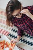Jeune femme mangeant une partie de pizza À l'intérieur, mode de vie Photographie stock libre de droits