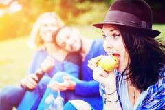 Jeune femme mangeant une poire et ayant le pique-nique avec des amis photos libres de droits