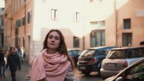 Jeune femme marchant à la rue ensoleillée de ville de ressort en Europe Fille élégante explorant la vieille seule ville banque de vidéos