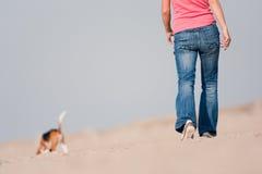 Jeune femme marchant avec le crabot sur la plage photo libre de droits