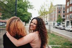 Jeune femme marchant avec son ami le long de rue de ville Image stock