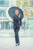 Jeune femme marchant avec un parapluie ouvert Image stock