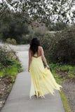 Jeune femme marchant dans la robe jaune à l'extérieur Photos libres de droits