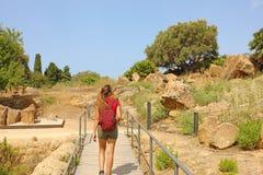 Jeune femme marchant dans la vallée des temples Agrigente, Sicile La fille de voyageur visite les temples grecs en Italie du sud image stock