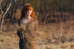 Jeune femme marchant dans le domaine d'herbe sèche d'or photographie stock libre de droits
