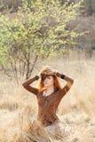 Jeune femme marchant dans le domaine d'herbe sèche d'or photo libre de droits