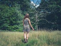 Jeune femme marchant dans le pré Photos libres de droits
