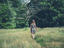 Jeune femme marchant dans le pré Photo stock