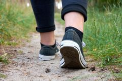 Jeune femme marchant dans les espadrilles et des jeans sur un chemin dans une forêt Image libre de droits