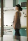 Jeune femme marchant dans une cuisine photographie stock
