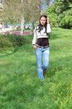 Jeune femme marchant en stationnement Photographie stock libre de droits