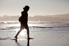 Jeune femme marchant le long de la plage Photographie stock libre de droits