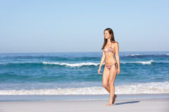 Jeune femme marchant le long de la plage sablonneuse Image stock