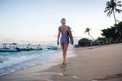 Jeune femme marchant le long du littoral avec le panneau de ressac Image stock